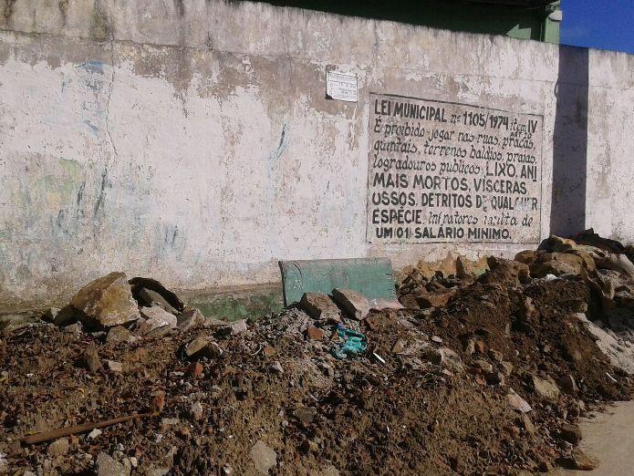 Entulho diante de muro com a lei municipal que proíbe o despejo desse tipo de material.