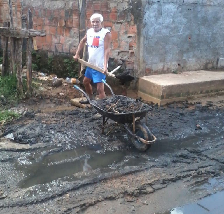 Idoso recolhe lama de esgoto acumulada na porta da sua casa.