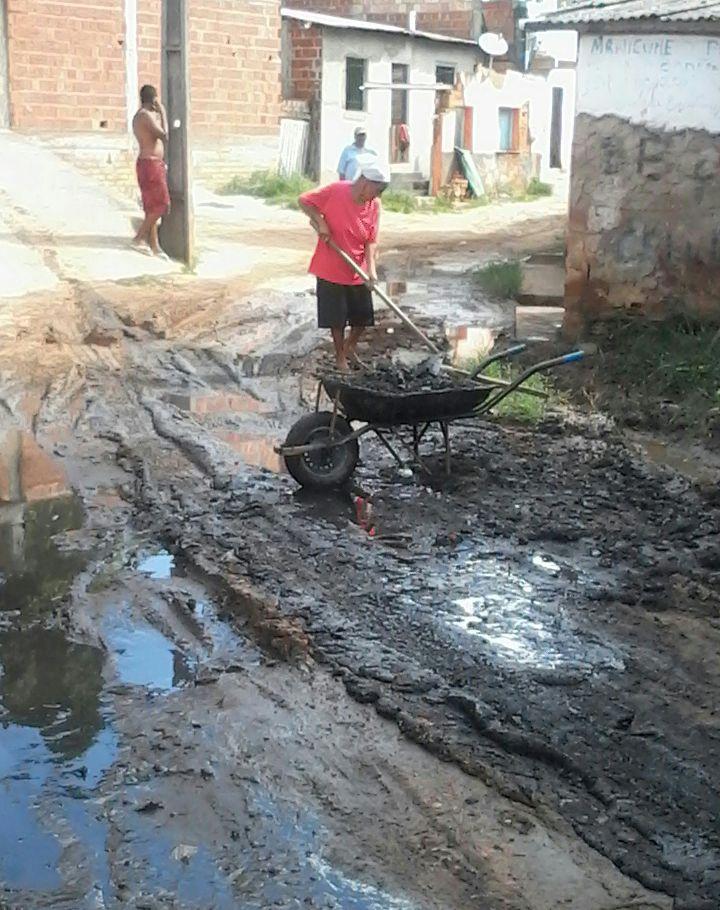 """Moradora  retira lama de esgoto da """"Rua da Horta""""."""
