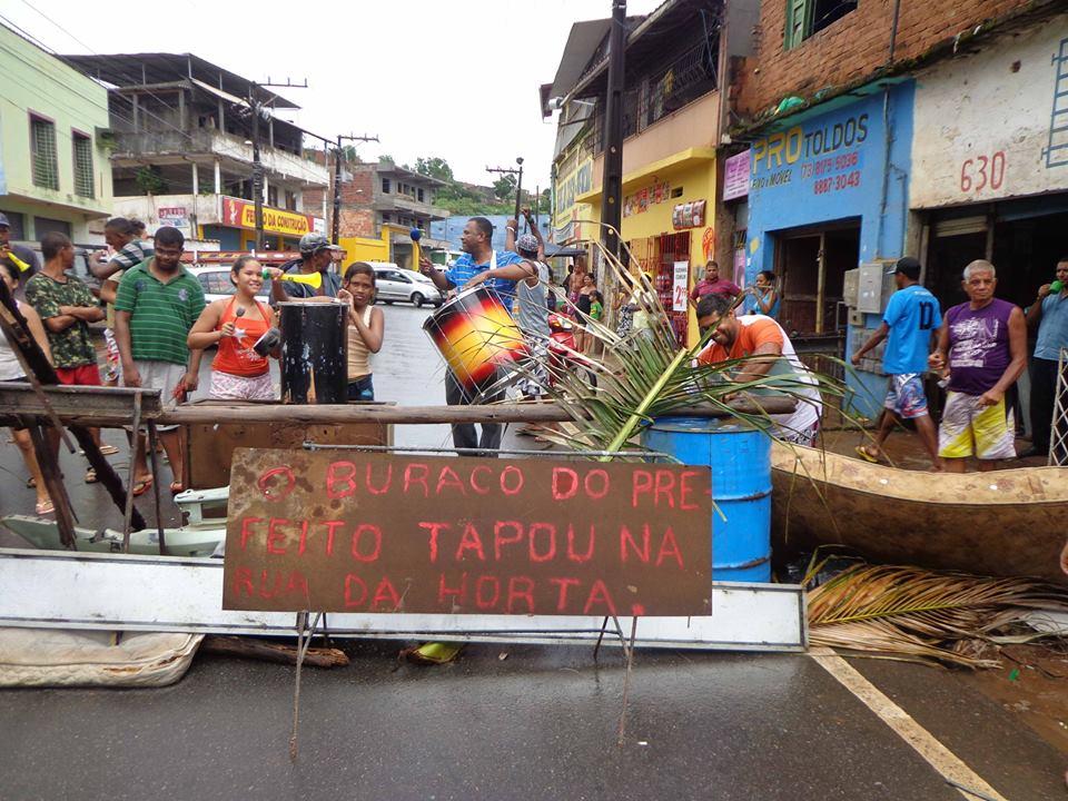 """O buraco do prefeito tapou na Rua da Horta"", diz a frase pintada na ""barricada"" de protesto que fechou a Avenida Ubaitaba, em Ilhéus."