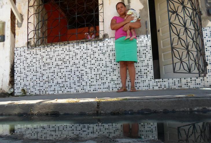 Daniela Lino e seu filho de seis meses diante da água suja acumulada na Rua Salgado Filho. Imagem: Thiago Dias/Blog do Gusmão.