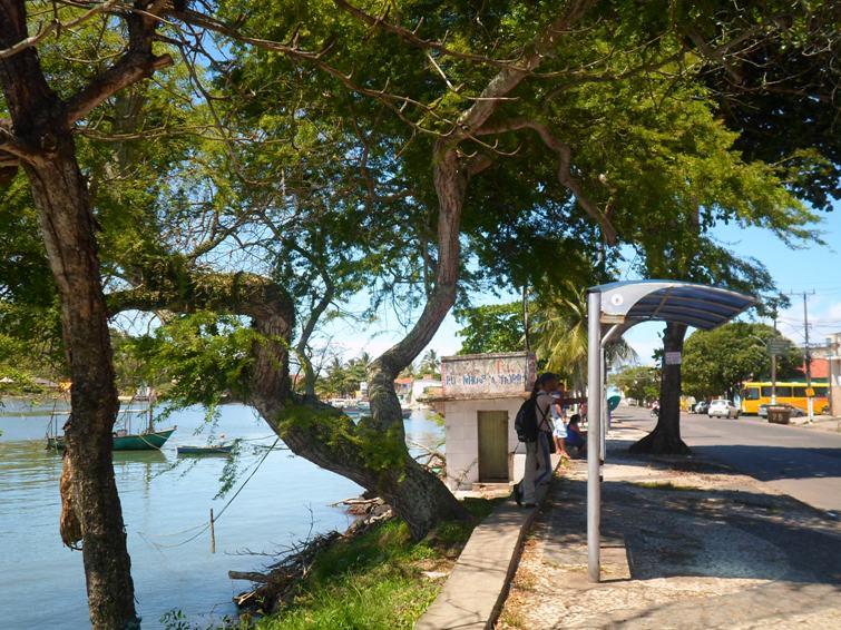 Ponto de ônibus sem assento na calçada esburacada da Avenida Lomanto Júnior, bairro Pontal, em Ilhéus. Imagem: Thiago Dias/Blog do Gusmão.