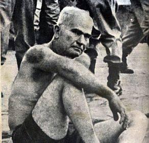 Gregório Bezerra de cuecas e com hematomas no rosto e no ombro, em 1º de abril de 1964. Vários militares no fundo.