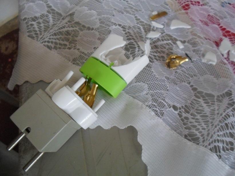 Estraçalhado pela bala, o adaptador de tomadas absorveu boa parte do impacto.
